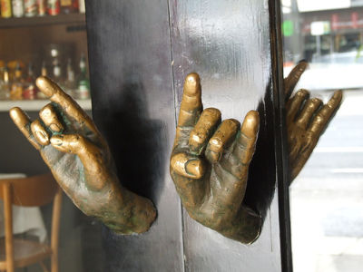 A Hand Door Knob Or A Door Knocker That Seems To Be Held Back By Hand